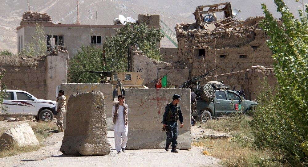 Афганский полицейский на фоне здания тюрьмы после нападения в провинции Газни, Афганистан 14 сентября 2015.