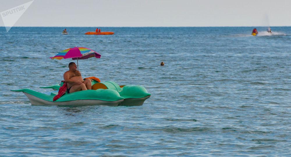Отдых туристов на пляже Черного моря в Абхазии