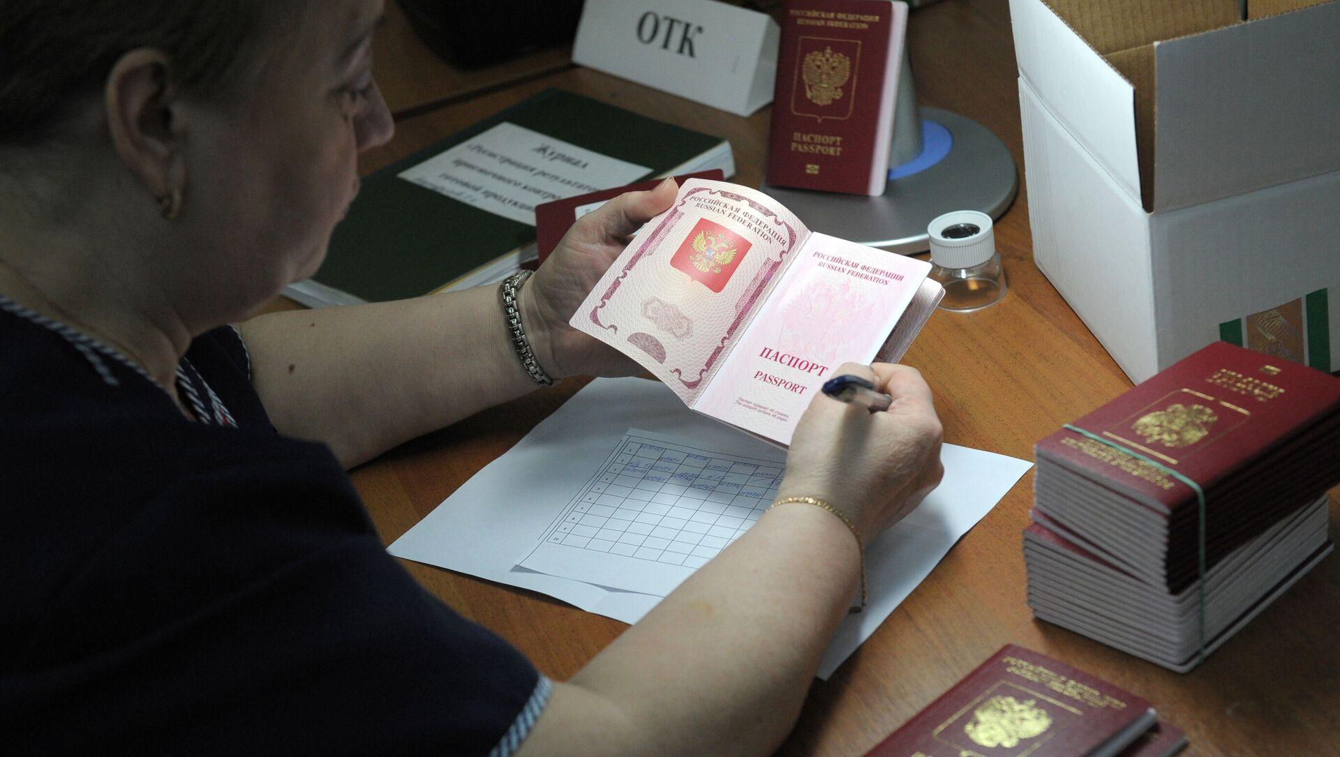 Сотрудница ФГУП Гознак проверяет качество готовых биометрических заграничных паспортов граждан РФ - Sputnik Аҧсны, 1920, 21.09.2021
