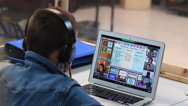 Учащиеся удаленно следят за онлайн-уроком своего обычного школьного учителя со стола, завернутого в защитный пластик, в Центре обучения и обогащения STAR Eco Station - Sputnik Аҧсны
