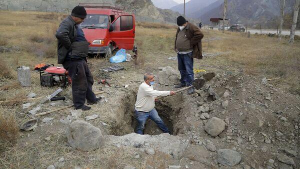 Местные жители села Кельбаджар выкапывают гроб с похороненным родственником, чтобы вывезти его останки - Sputnik Абхазия