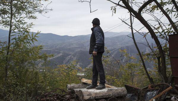 Мужчина смотрит на горы возле своего дома в поселке Карегах - Sputnik Абхазия