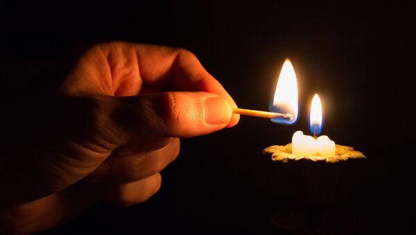 Человек зажигает свечу - Sputnik Абхазия