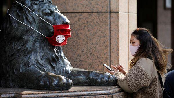 Женщина в защитной маске перед статуей в Токио  - Sputnik Абхазия