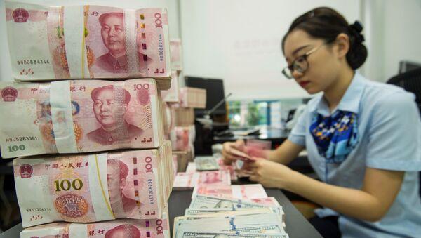 Сотрудник китайского банка считает банкноты 100 юаней и долларовые банкноты на кассе банка в Наньтуне в восточной провинции Китая Цзянсу 28 августа 2019 г. - Валюта Китая упала 26 августа до самой слабой точки за более чем 11 лет из-за опасений по поводу Торговая война США и возможность глобальной рецессии оказали давление на рынки - Sputnik Абхазия