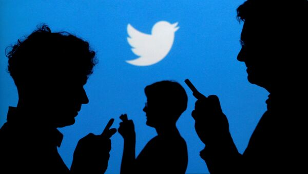 Люди в руках с мобильными телефонами вырисовываются на фоне, на котором изображен логотип Twitter, на этой фотографии, сделанной 27 сентября 2013 года - Sputnik Абхазия