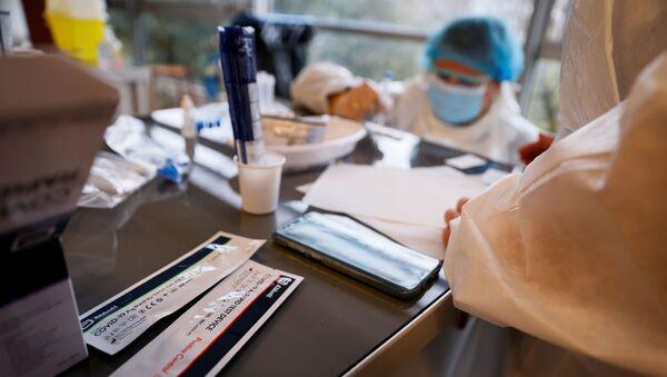 Наборы для тестирования антигена лежат на столе, пока медицинский работник проводит тест во время операции по массовому скринингу на Covid-19 - Sputnik Аҧсны