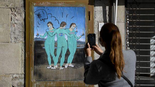 Женщина фотографирует на свой мобильный телефон новую работу итальянского уличного художника TvBoy под названием «Три вакцины», на которой изображена картина итальянского художника Рафаэля «Три грации», в Барселоне, 19 января 2021 года - Sputnik Абхазия