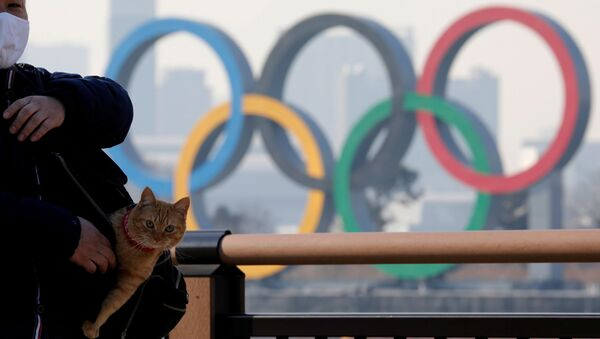 Мужчина с котом в сумке на фоне олимпийских колец в Токио - Sputnik Абхазия