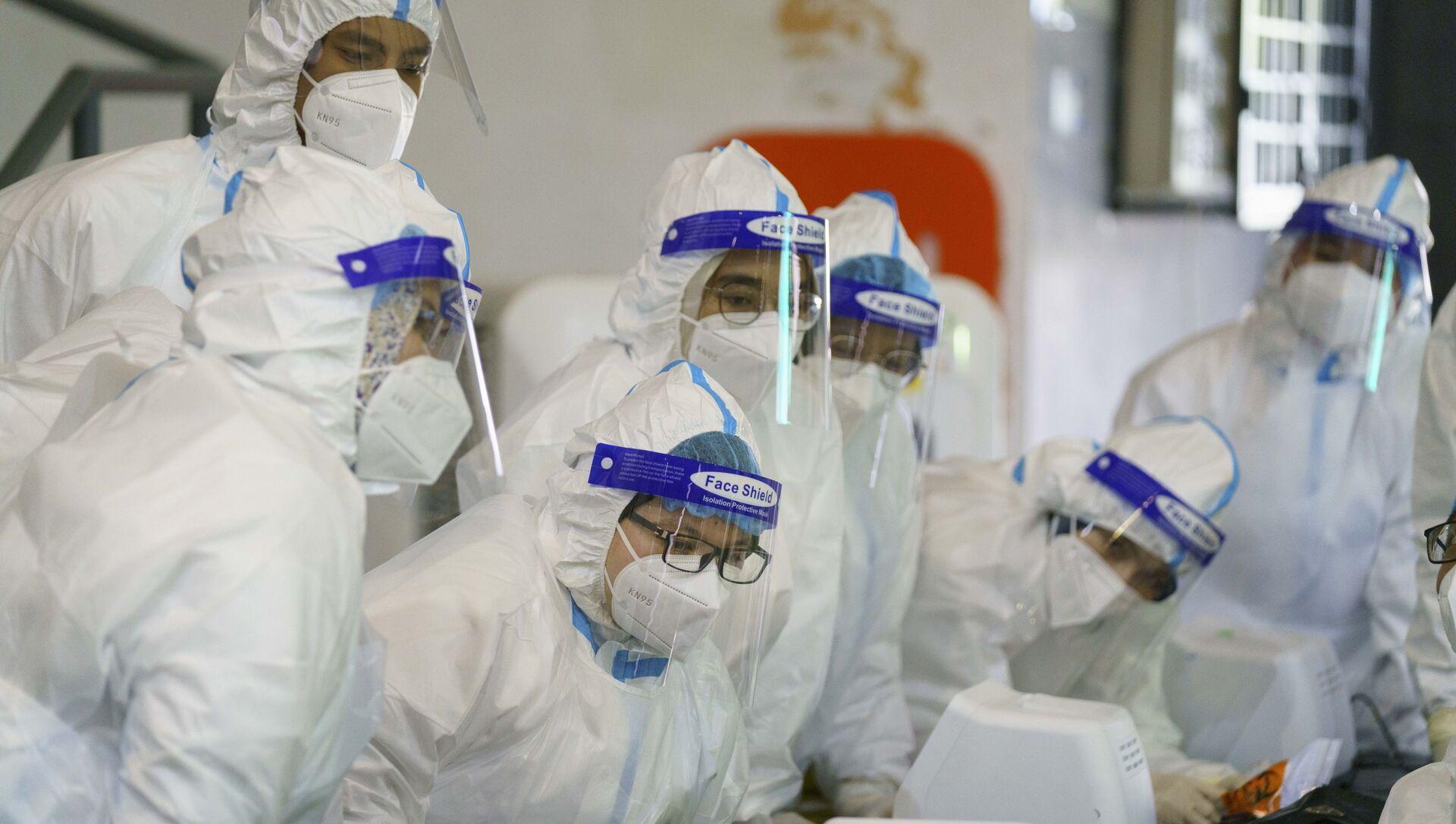 Медицинский работник в средствах индивидуальной защиты (СИЗ) слушает брифинг в центре тестирования на COVID-19 в городе Шах-Алам - Sputnik Аҧсны, 1920, 24.02.2021