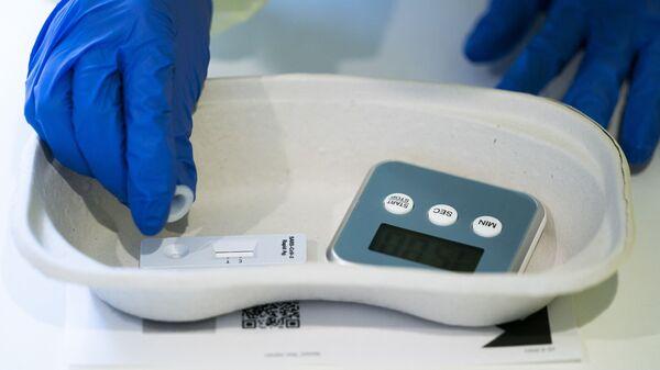 Медицинский работник обрабатывает экспресс-тест на Covid-19 - Sputnik Аҧсны