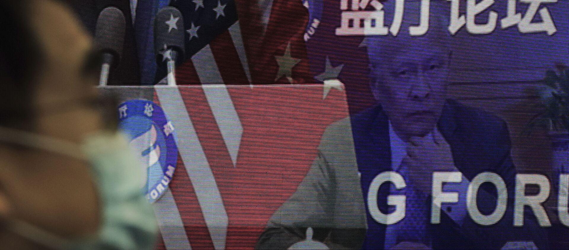 Мужчина в маске, помогающей сдержать распространение коронавируса, сидит возле экрана, демонстрирующего, как делегаты присутствуют на форуме Лантинга, посвященном приезду Китая и США. отношения вернулись в правильное русло, которое под председательством министра иностранных дел Китая Ван И в офисе Министерства иностранных дел в Пекине в понедельник, 22 февраля 2021 года. В понедельник Ван призвал США снять ограничения на торговлю и контакты между людьми при прекращении того, что Пекин считает необоснованным вмешательством в районы Тайваня, Гонконга, Синьцзяна и Тибета - Sputnik Абхазия, 1920, 16.04.2021