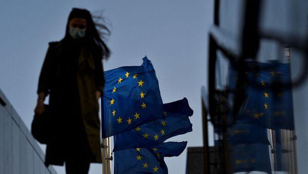 Женщина в защитной маске идет перед флагом Европейского Союза в районе штаб-квартиры ЕС в Брюсселе, 23 февраля 2021 г - Sputnik Абхазия