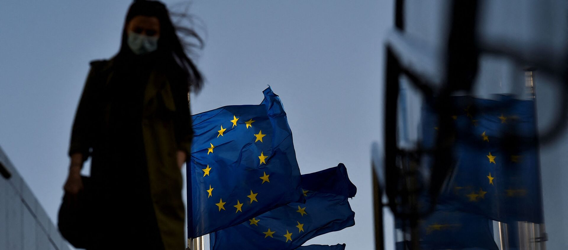 Женщина в защитной маске идет перед флагом Европейского Союза в районе штаб-квартиры ЕС в Брюсселе, 23 февраля 2021 г - Sputnik Абхазия, 1920, 27.05.2021