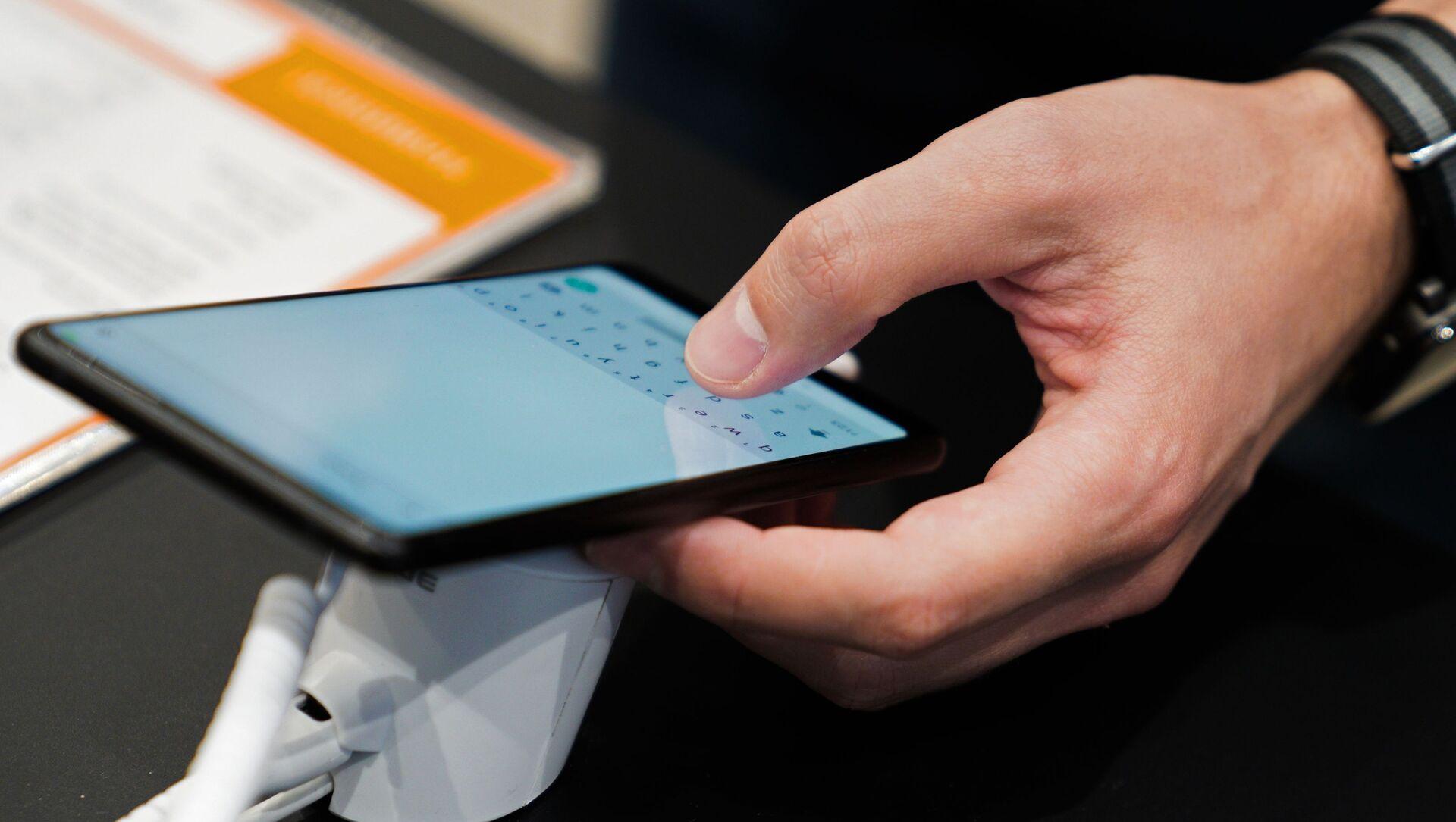 Посетитель осматривает смартфон в магазине Xiaomi на Тверской улице в Москве. Компания Xiaomi открыла новый официальный круглосуточный магазин в Москве. - Sputnik Абхазия, 1920, 13.09.2021