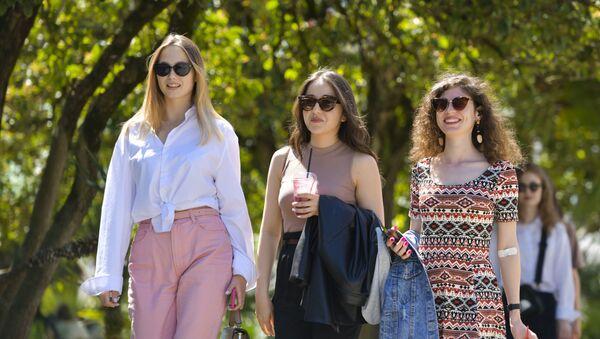 Девушки прогуливаются по набережной в солнечную погоду  - Sputnik Аҧсны
