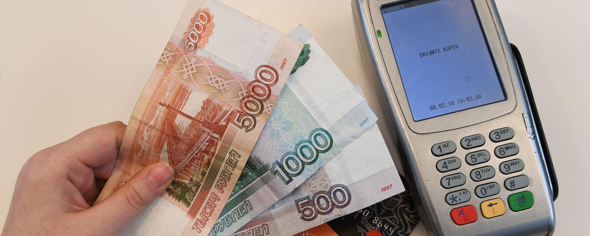 Терминал оплаты банковскими картами и денежные купюры. - Sputnik Абхазия, 1920, 17.05.2021
