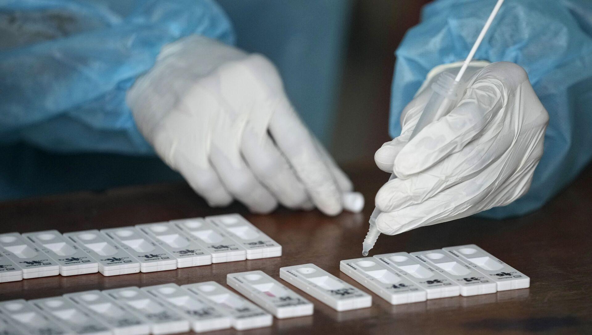 Медицинский работник проверяет образцы мазков из носа на коронавирус во время массового тестирования в Бекаси на окраине Джакарты - Sputnik Аҧсны, 1920, 22.07.2021