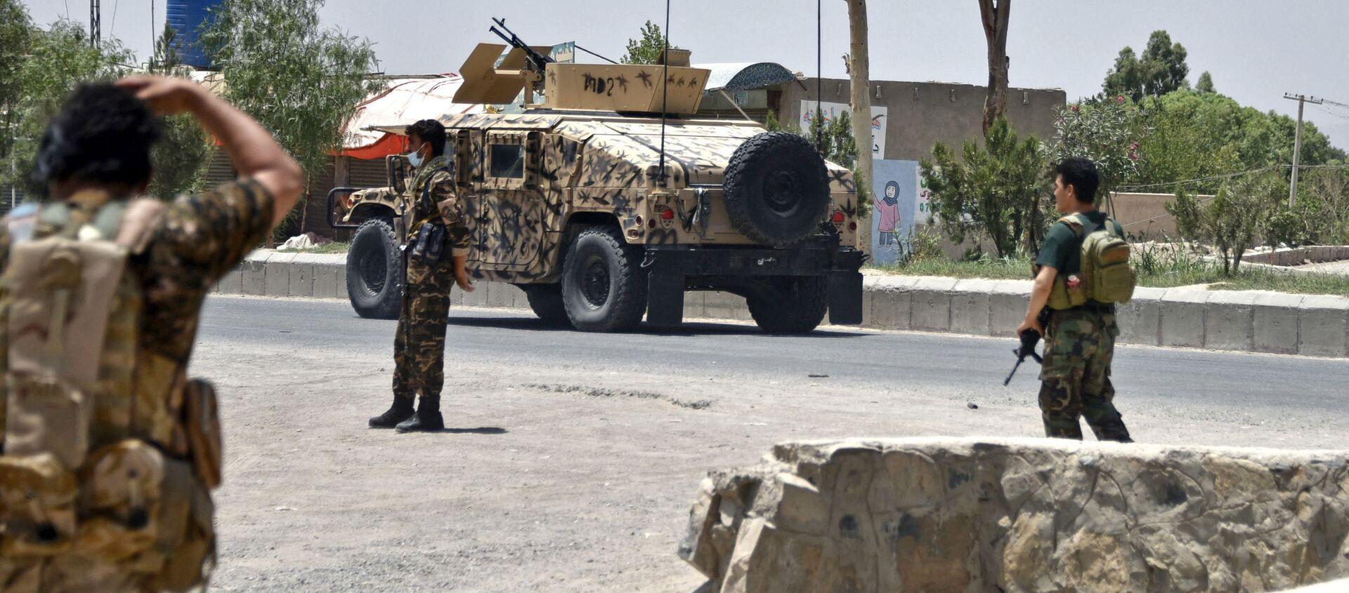 Афганские службы безопасности стоят на страже дороги на фоне продолжающейся борьбы между афганскими силами безопасности и боевиками Талибана в Кандагаре 9 июля 2021 г - Sputnik Абхазия, 1920, 15.07.2021