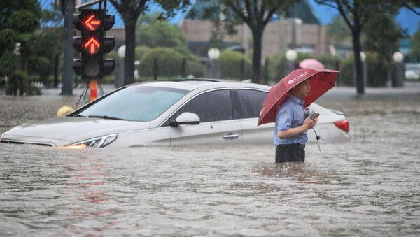 Мужчина у затопленной в результате проливных дождей машины после проливных дождей в Чжэнчжоу в центральной провинции Китая Хэнань - Sputnik Абхазия