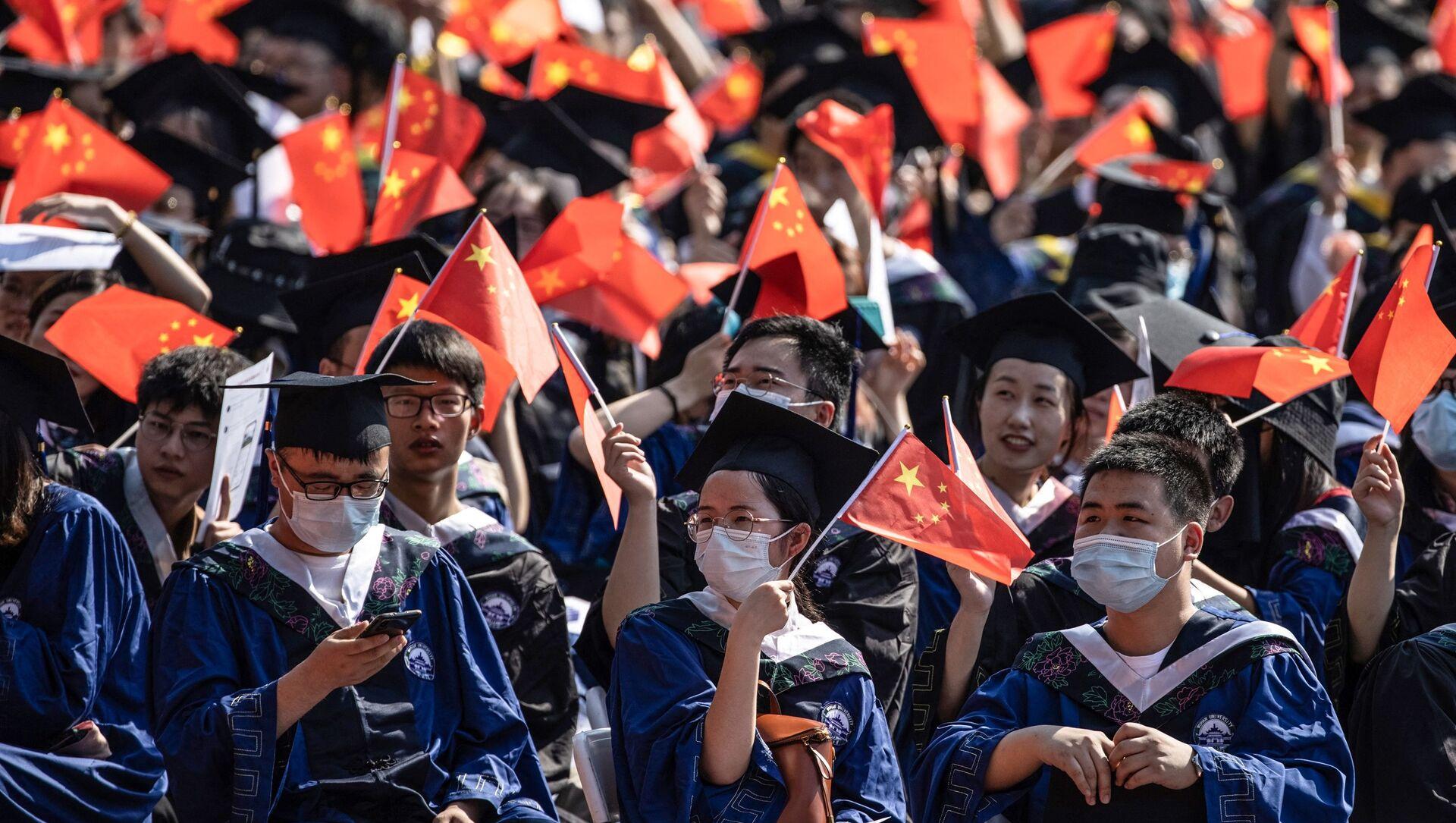Выпускники Уханьского университета размахивают национальными флагами на церемонии выпуска в Ухане, в центральной китайской провинции Хубэй - Sputnik Абхазия, 1920, 29.07.2021