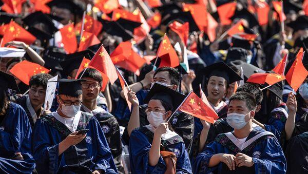 Выпускники Уханьского университета размахивают национальными флагами на церемонии выпуска в Ухане, в центральной китайской провинции Хубэй - Sputnik Абхазия