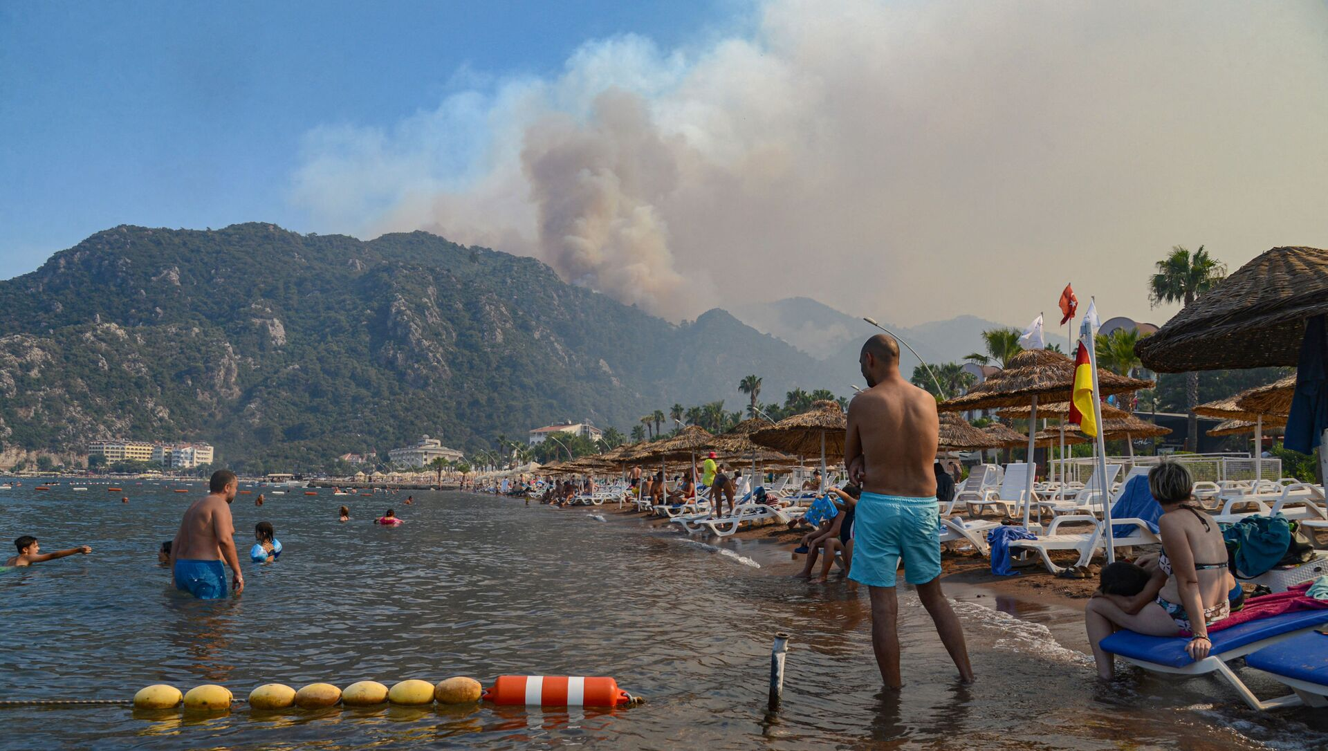 С пляжа туристы наблюдают за мощным лесным пожаром, охватившим курортный регион Средиземноморья, на южном побережье Турции, недалеко от Мармариса, 30 июля 2021 года. пожарные тушили пожар, охвативший курортный регион Средиземноморья на южном побережье Турции. Официальные лица также начали расследование подозрений в том, что пожары, возникшие в среду в четырех местах к востоку от туристической точки Анталии, были результатом поджога. - Sputnik Абхазия, 1920, 31.07.2021