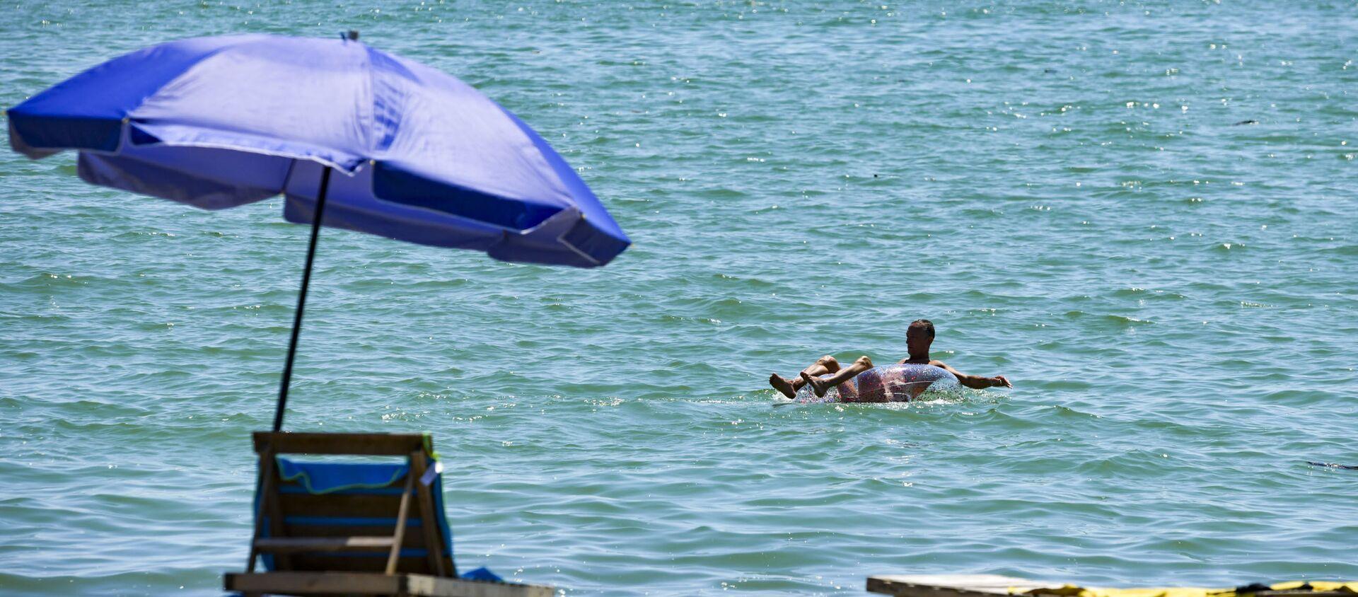 Мужчина купается на круге в море  - Sputnik Абхазия, 1920, 04.08.2021