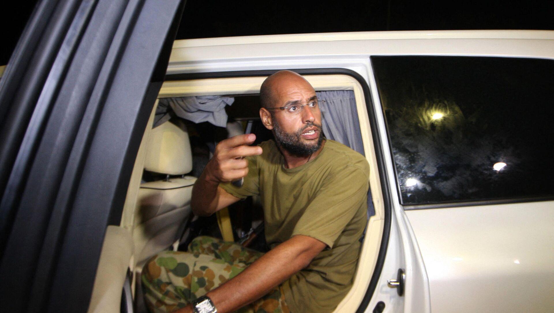 На этой файловой фотографии, сделанной 23 августа 2011 года, изображен Саиф аль-Ислам, сын покойного ливийского диктатора Моамера Каддафи, жестикулирующий, когда он появляется перед сторонниками и журналистами в жилом комплексе своего отца в столице Ливии Триполи в начале часы. - Саиф аль-Ислам Каддафи, которого когда-то считали преемником своего отца, не видел и не слышал публично с тех пор, как десять лет назад он был схвачен в ливийской пустыне. Он разговаривал с международными СМИ и говорит, что хочет стать президентом Ливии. - Sputnik Абхазия, 1920, 04.08.2021