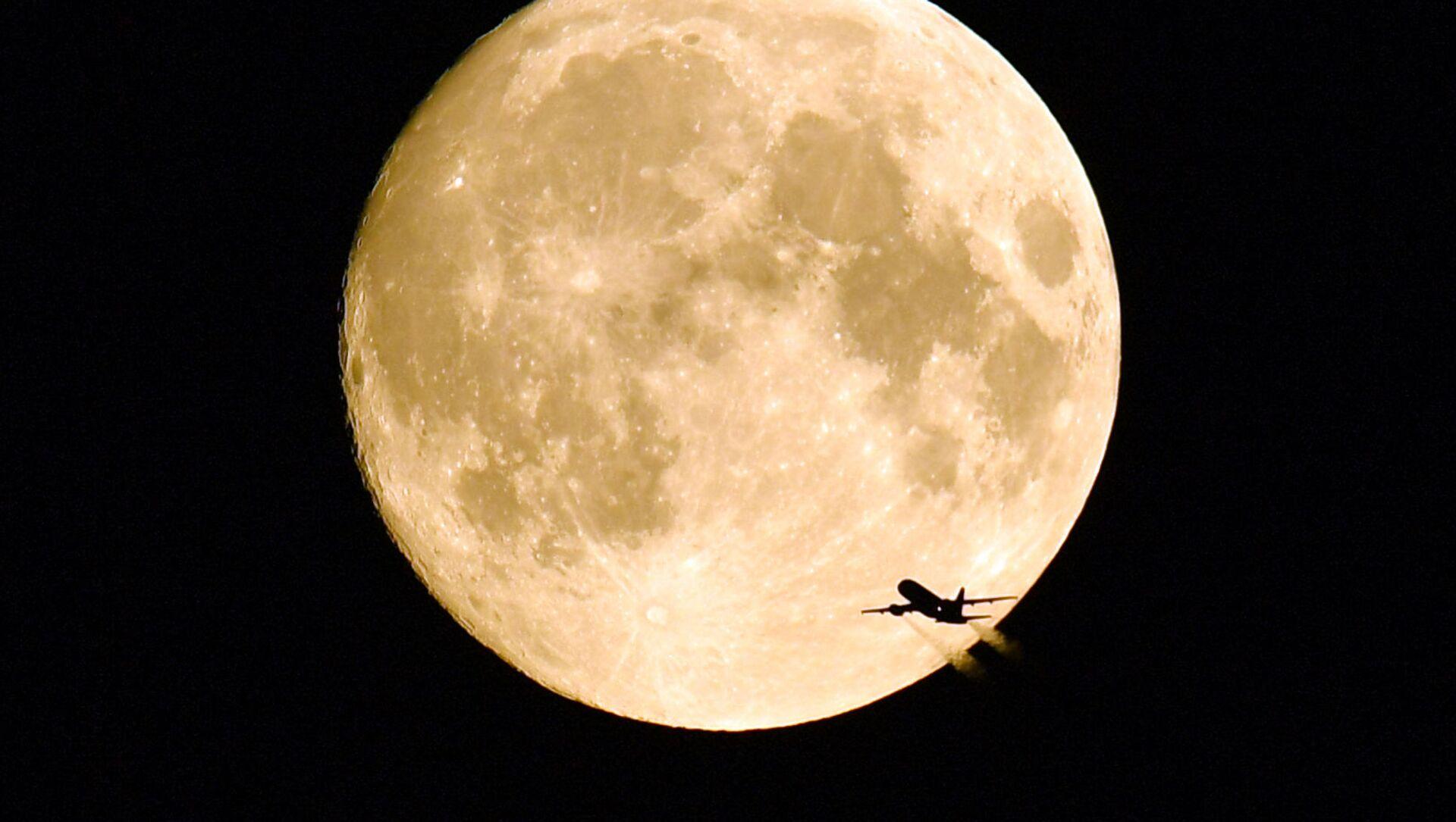 Летящий самолет на фоне полной Луны. - Sputnik Абхазия, 1920, 13.08.2021