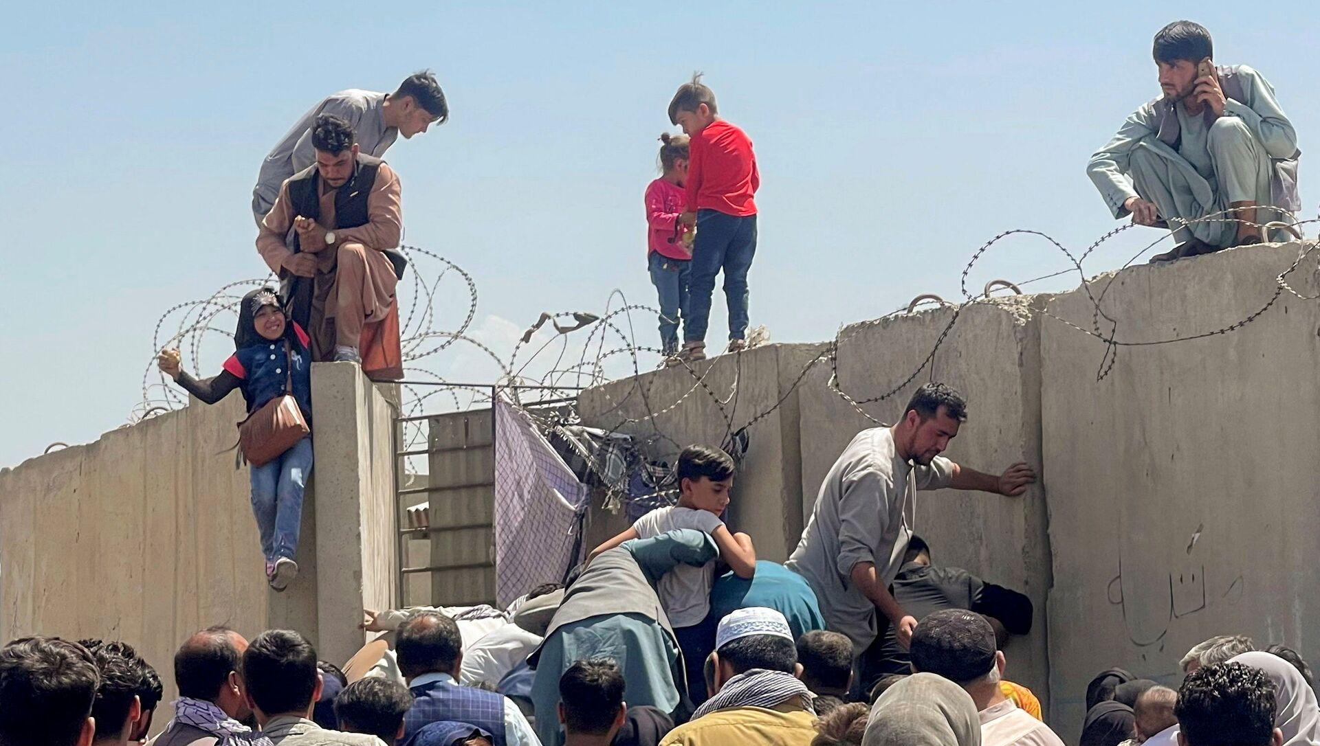 Мужчина тянет девушку, чтобы попасть в международный аэропорт имени Хамида Карзая в Кабуле, Афганистан, 16 августа 2021 года. - Sputnik Абхазия, 1920, 16.08.2021