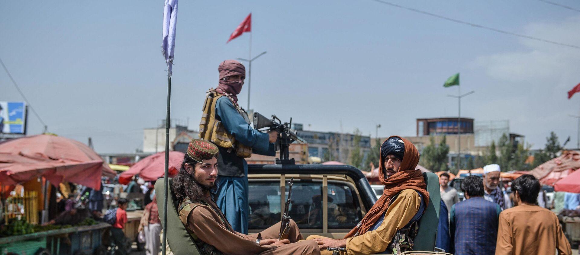 Боевики Талибана на пикапе передвигаются по рыночной площади, стекаясь с местными афганцами в районе Котэ Санги в Кабуле - Sputnik Абхазия, 1920, 17.08.2021
