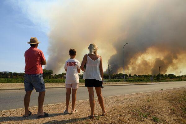 Туристы наблюдают с обочины дороги густой дым от возобновившихся лесных пожаров к северу от Гримо, на юге Франции - Sputnik Абхазия