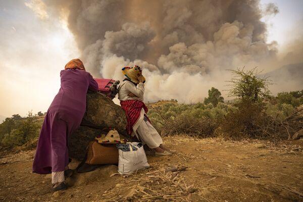 Женщины на горной дороге со своими вещами во время лесных пожаров на севере Марокко. - Sputnik Абхазия