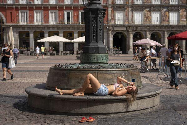 Девушка загорает на скамейке на площади во время сильной жары в Мадриде, Испания. - Sputnik Абхазия
