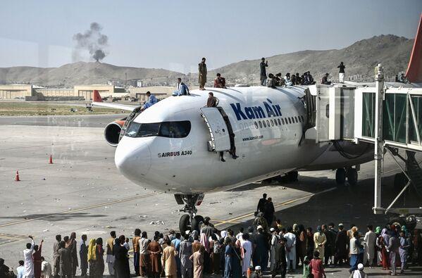 Афганцы забираются на самолет в аэропорту после вступления талибов в Кабул. - Sputnik Абхазия