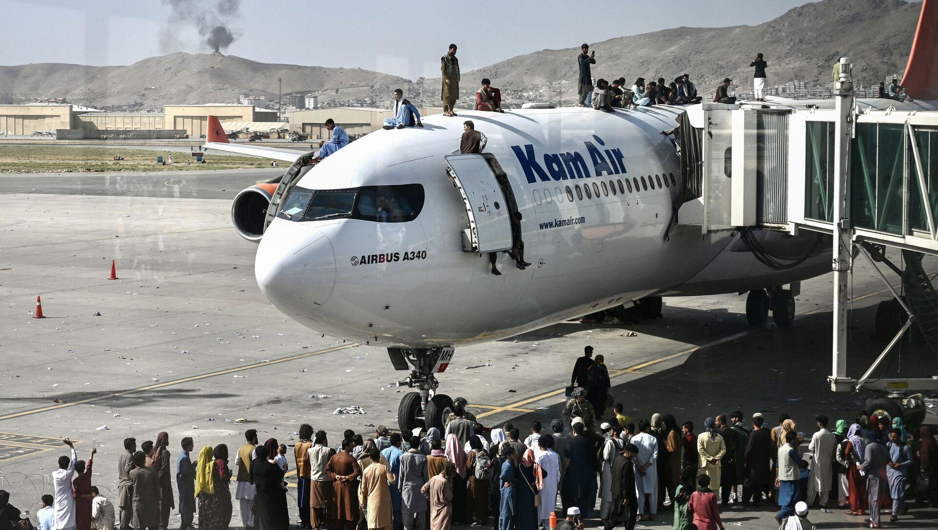 Афганцы забираются на самолет в аэропорту после вступления талибов в Кабул - Sputnik Абхазия, 1920, 31.08.2021
