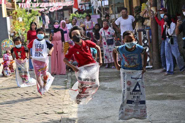 Дети в масках принимают участие в соревнованиях по бегу на мешках во время празднования Дня независимости в Джакарте, Индонезия. - Sputnik Абхазия