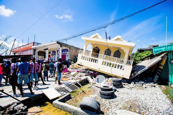 Люди стоят рядом с домом, разрушенным в результате землетрясения силой 7,2 балла в Ле-Ке, Гаити. - Sputnik Абхазия
