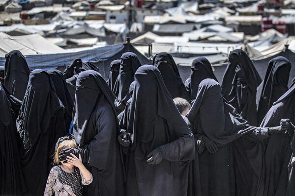 Женщины с детьми выстраиваются в очередь, чтобы получить посылки с гуманитарной помощью в управляемом курдами лагере Аль-Хол, где содержатся родственники предполагаемых боевиков группировки Исламское государство*, в сирийской провинции Хасакех. - Sputnik Абхазия