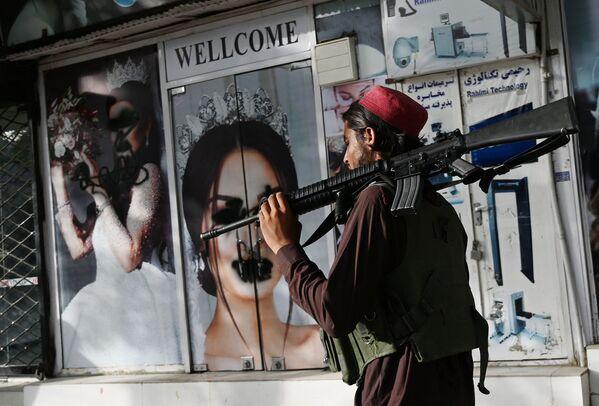 Боевик Талибана* у салона красоты с изображениями женщин, испачканных аэрозольной краской, в Шахр-э Нау в Кабуле. - Sputnik Абхазия