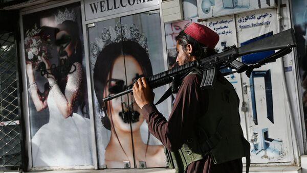 Боевик Талибана* у салона красоты с изображениями женщин, испачканных аэрозольной краской, в Шахр-э Нау в Кабуле - Sputnik Абхазия