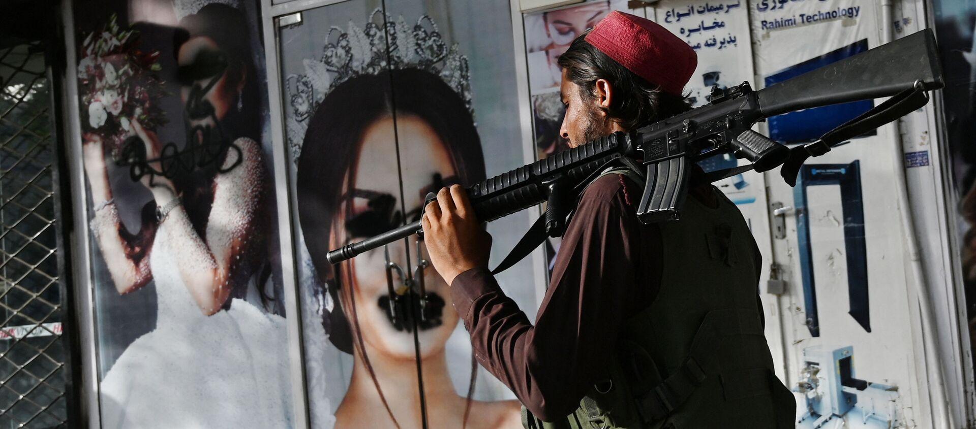 Боевик Талибана* у салона красоты с изображениями женщин, испачканных аэрозольной краской, в Шахр-э Нау в Кабуле - Sputnik Абхазия, 1920, 02.09.2021