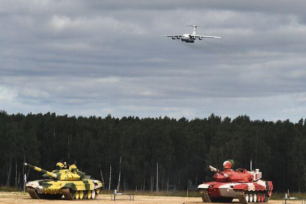 Танки Т-72Б3 команд военнослужащих Узбекистана (слева) и Китая во время соревнований танковых экипажей в рамках конкурса Танковый биатлон-2021 на полигоне Алабино в Подмосковье в рамках VII Армейских международных игр АрМИ-2021. На втором плане – грузовой самолет Ил-76МД. - Sputnik Абхазия