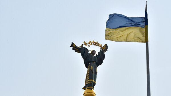 Украинский флаг развевается перед Монументом Независимости в столице Украины Киеве 29 марта 2019 года в преддверии президентских выборов 31 марта - Sputnik Абхазия