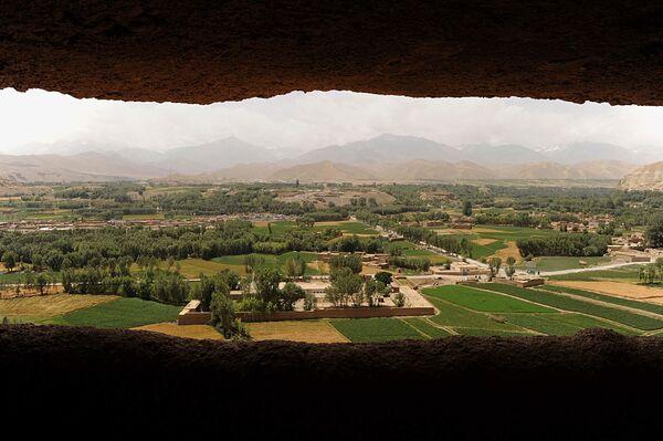 Общий вид на город через одну из двух пустых ниш статуй Будды, которые были разрушены талибами* в 2001 году, Бамиан. - Sputnik Абхазия