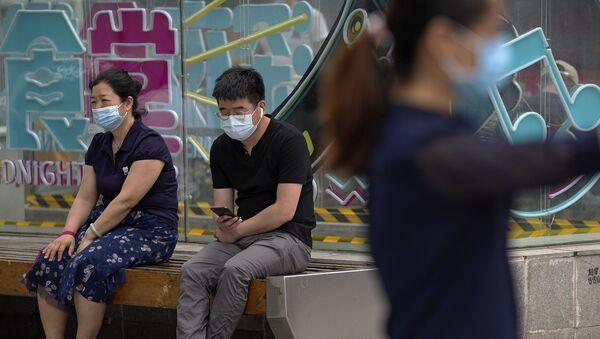 Люди, носящие маски для лица, чтобы помочь обуздать распространение коронавируса, отдыхают на скамейке возле торгового центра в Пекине в понедельник, 24 мая 2021 г. - Sputnik Абхазия