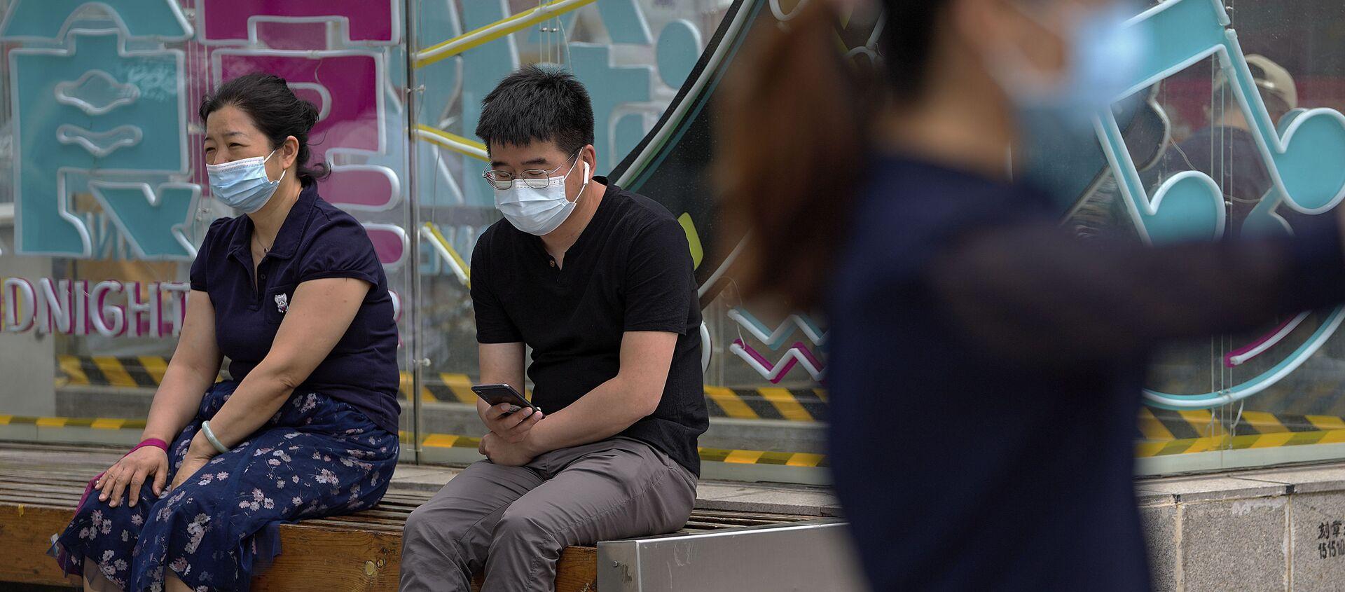 Люди, носящие маски для лица, чтобы помочь обуздать распространение коронавируса, отдыхают на скамейке возле торгового центра в Пекине в понедельник, 24 мая 2021 г. - Sputnik Абхазия, 1920, 28.08.2021