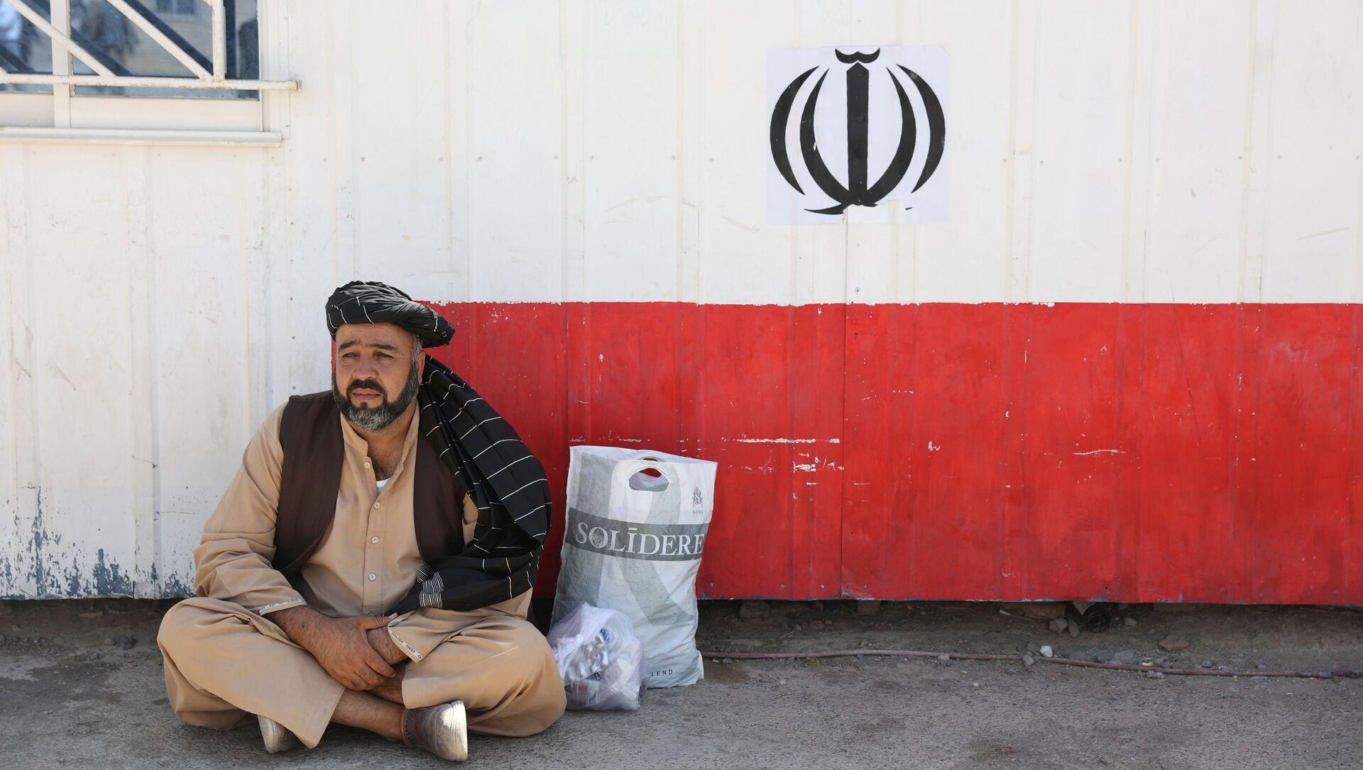 Афганец сидит на пограничном переходе Даукарун между Ираном и Афганистаном - Sputnik Абхазия, 1920, 03.09.2021
