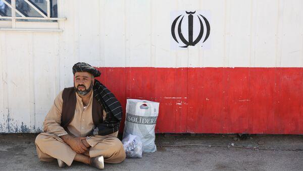 Афганец сидит на пограничном переходе Даукарун между Ираном и Афганистаном - Sputnik Абхазия
